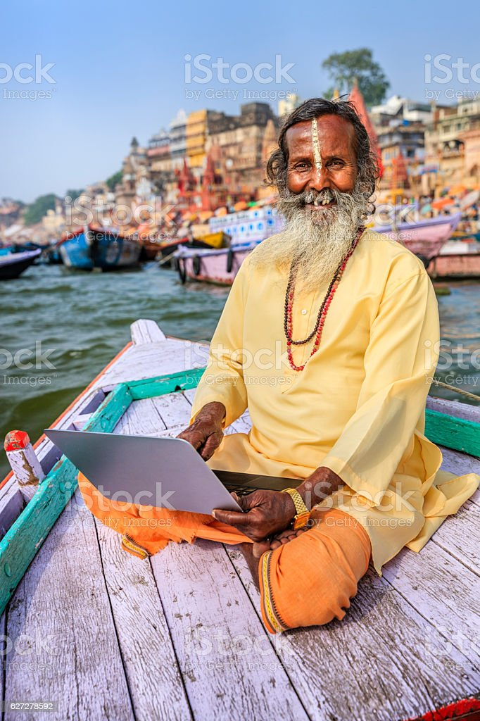 Sadhu using laptop in boat on Holy Ganges River, Varanasi stock photo