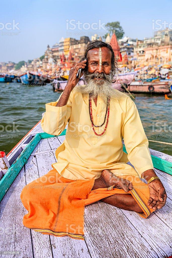 Sadhu using mobile in boat on Holy Ganges River, Varanasi stock photo