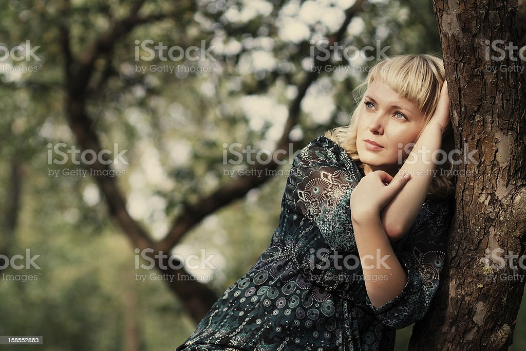 Sadness girl sitting on a tree branch royalty-free stock photo
