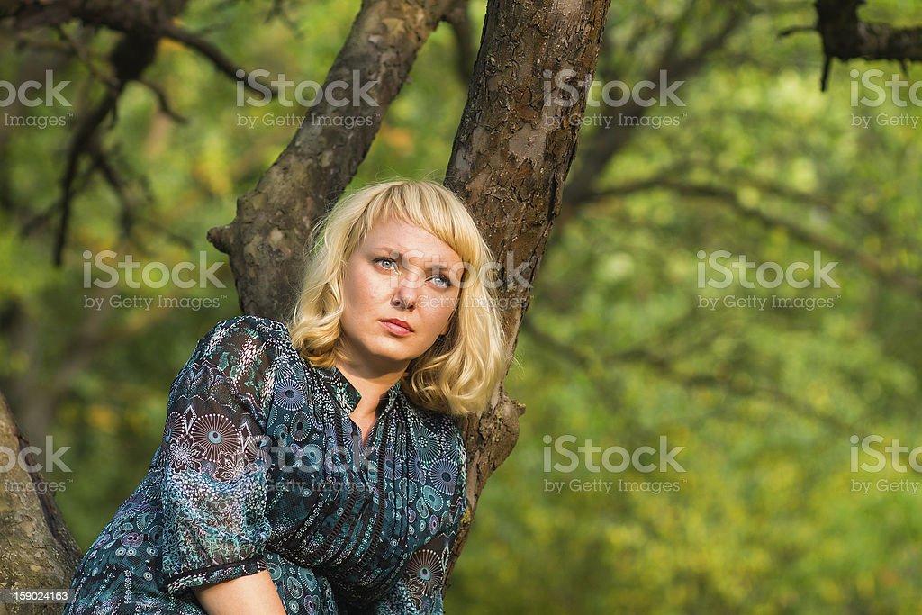 Sadness woman sitting on a tree branch royalty-free stock photo