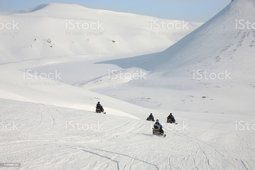 Safari on snowmobiles in arctic mountains of Svalbard, Norway royalty-free stock photo