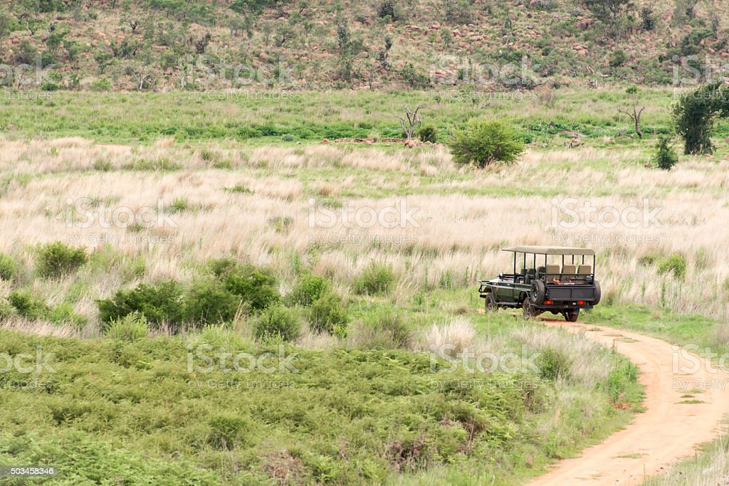 Safari vehicle riding a red dirt road in Africa stock photo