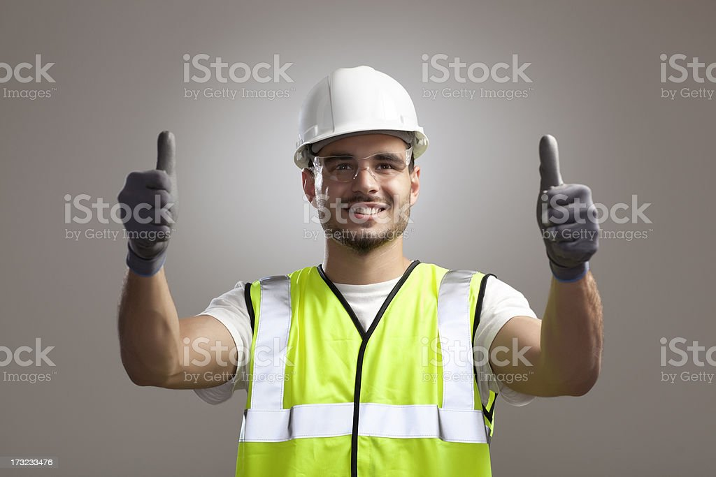 Portrait of happy manual worker man in protective gear gesturing...