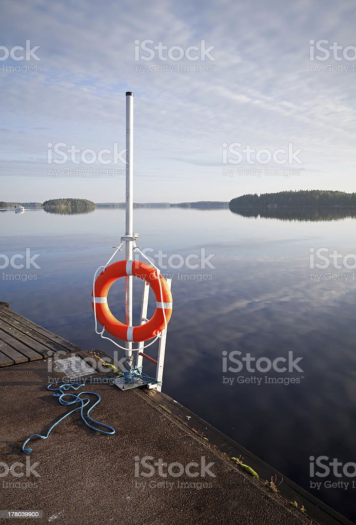 Safety equipment. Bright red lifebuoy on the pier royalty-free stock photo