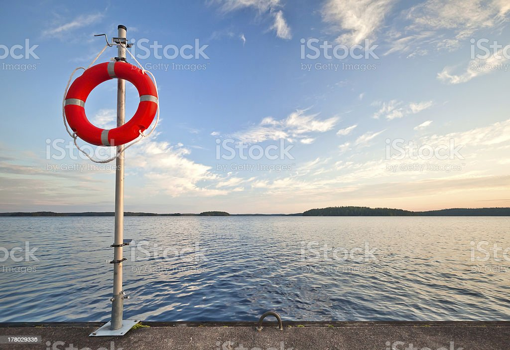 Safety equipment. Bright red safe lifebuoy on the pier royalty-free stock photo