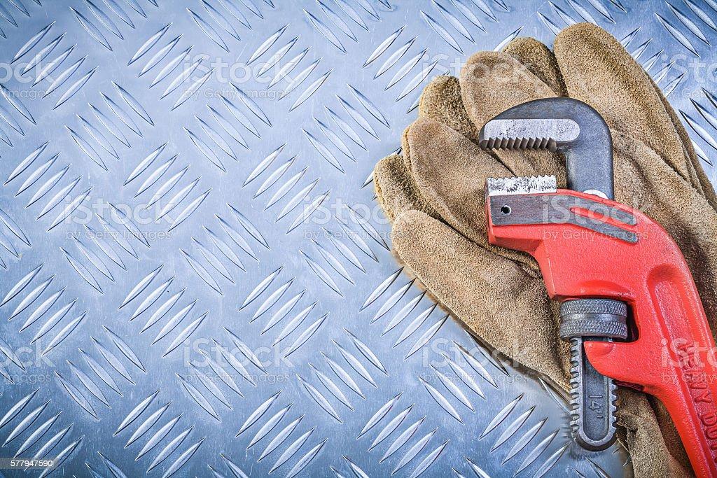 Safety gloves monkey wrench on corrugated metallic sheet copyspa stock photo