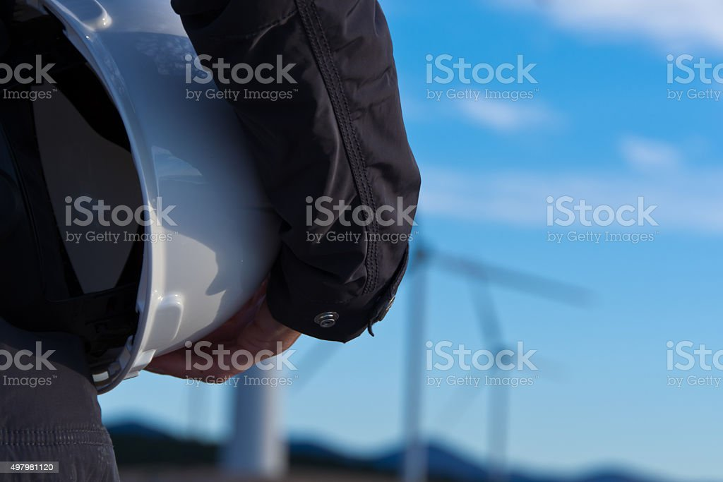 safety helmet and wind turbines in the background stock photo