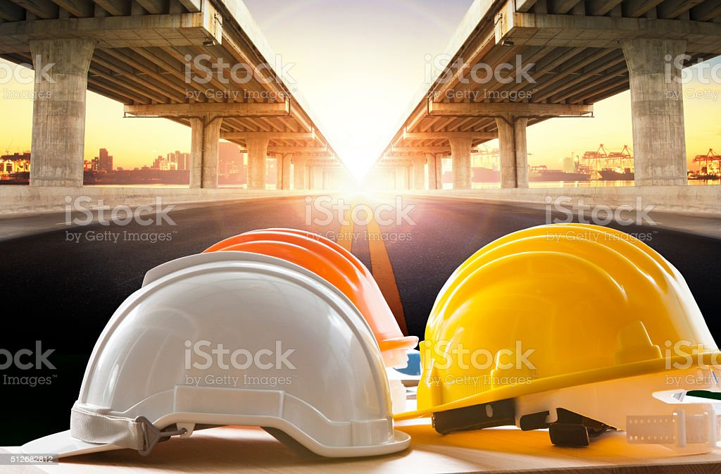 safety helmet on civil engineering working table against bridge stock photo