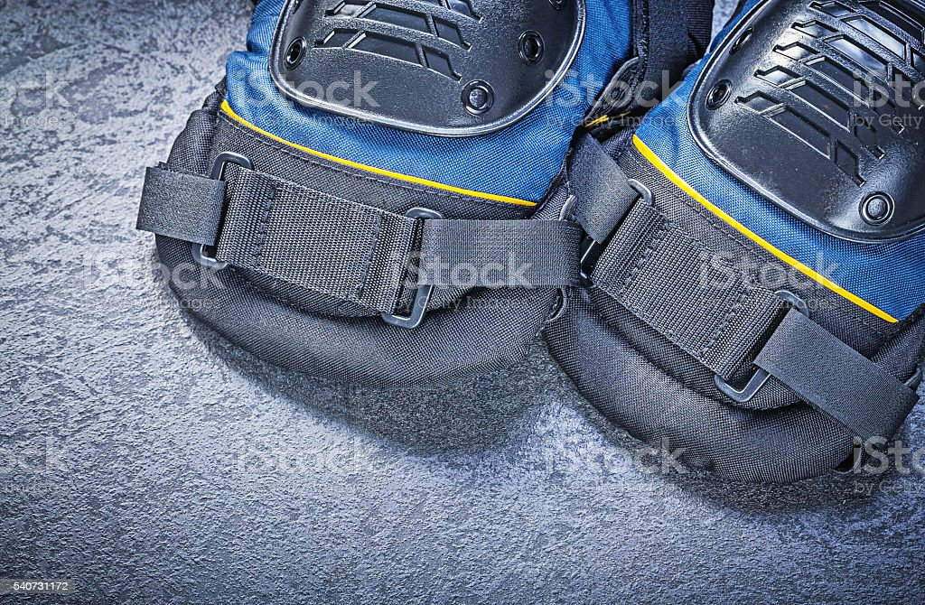 Safety knee pads on black background construction concept stock photo