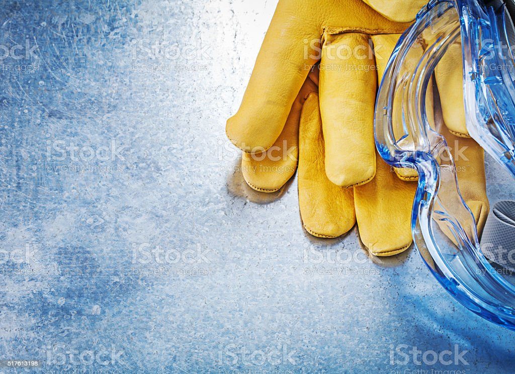 Safety spectacles gloves on scratched metallic background constr stock photo
