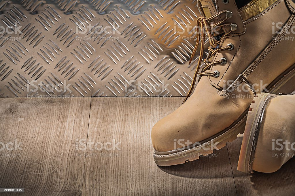 Safety waterproof lace boots wooden board channeled metal plate stock photo