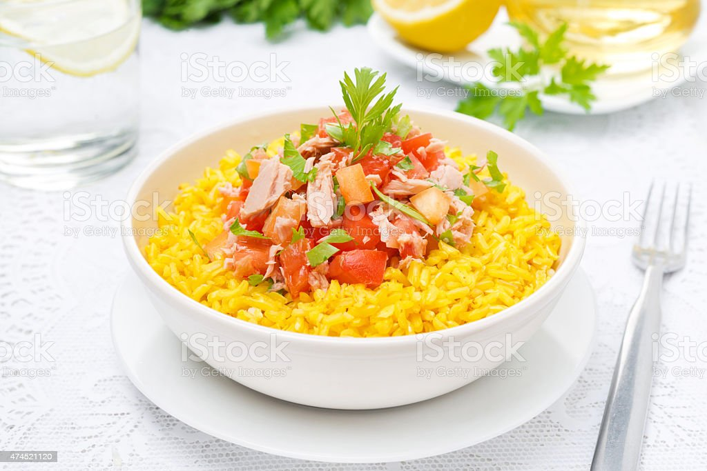 saffron rice with tuna, tomatoes, peppers and herbs in bowl stock photo
