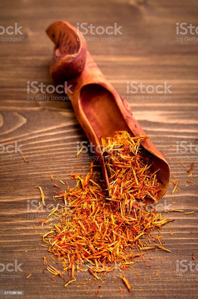Saffron spice threads in scoop on wooden background stock photo