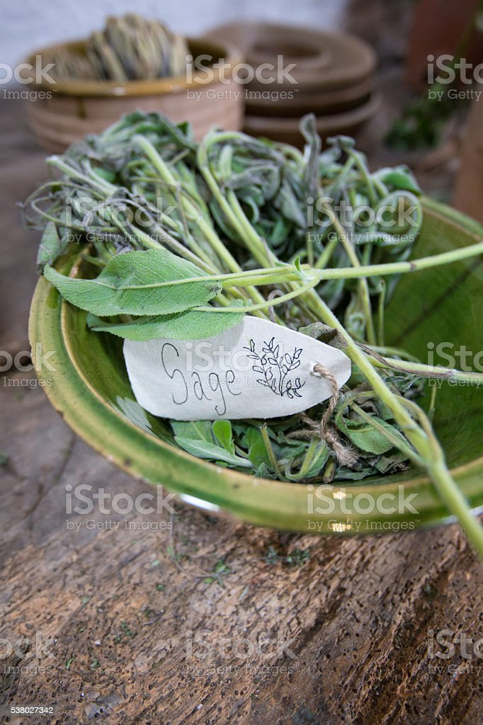 Sage leaves in a bowl on a rustic wooden table stock photo