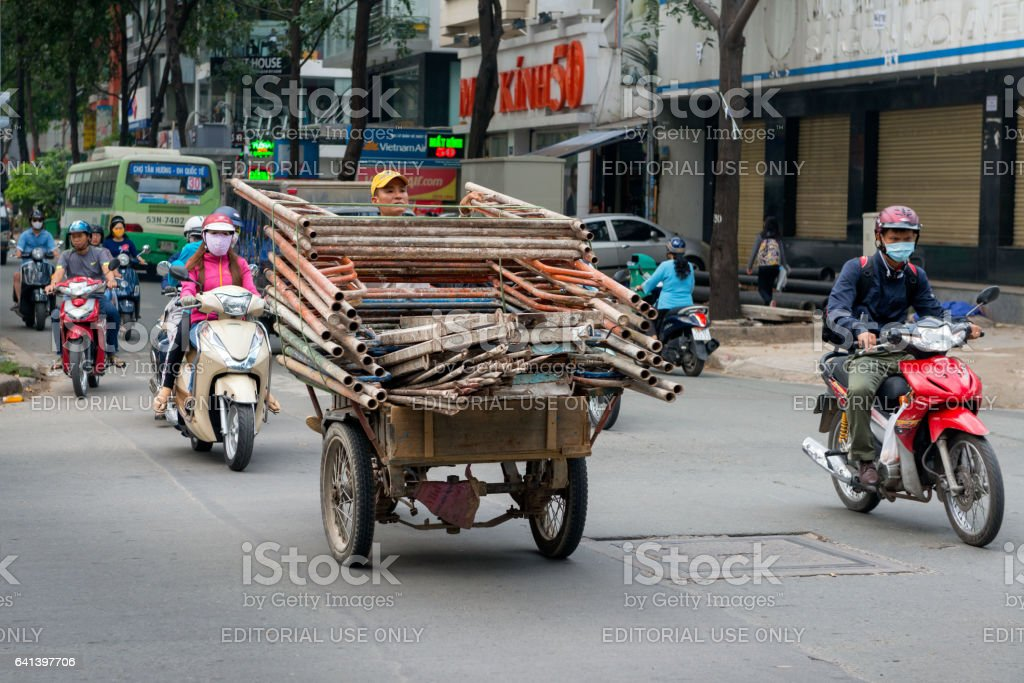 Saigon, Vietnam - Man riding overloaded scooter transporting scaffolding stock photo