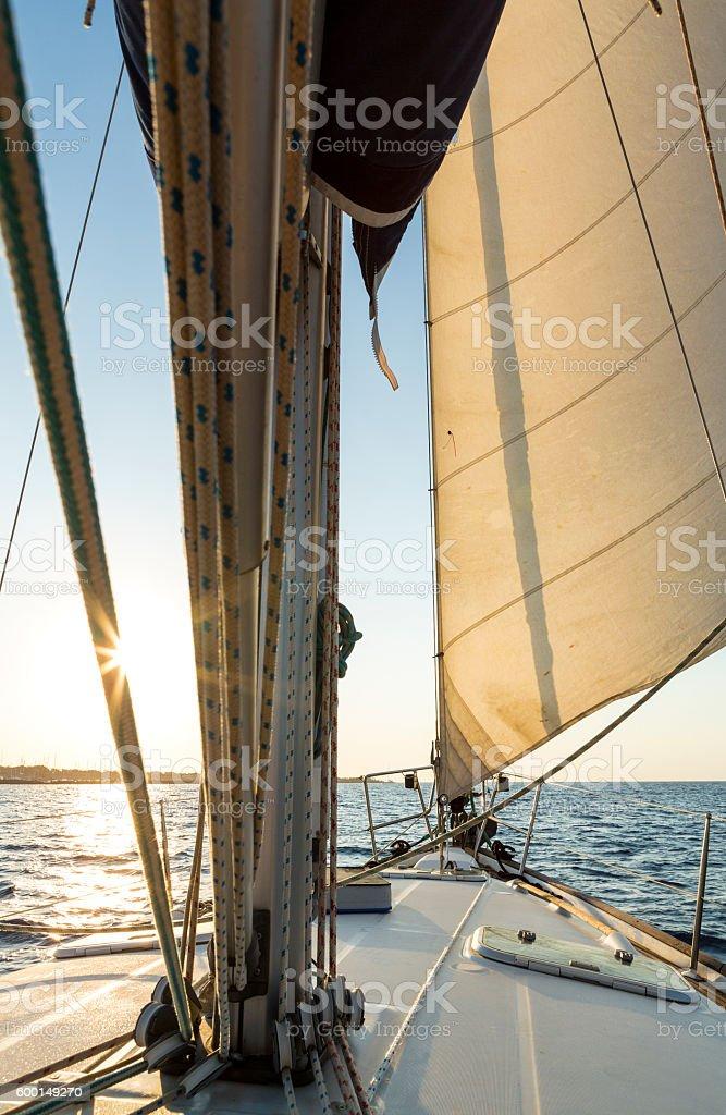 Sail boat cruising at sunrise with full sails stock photo