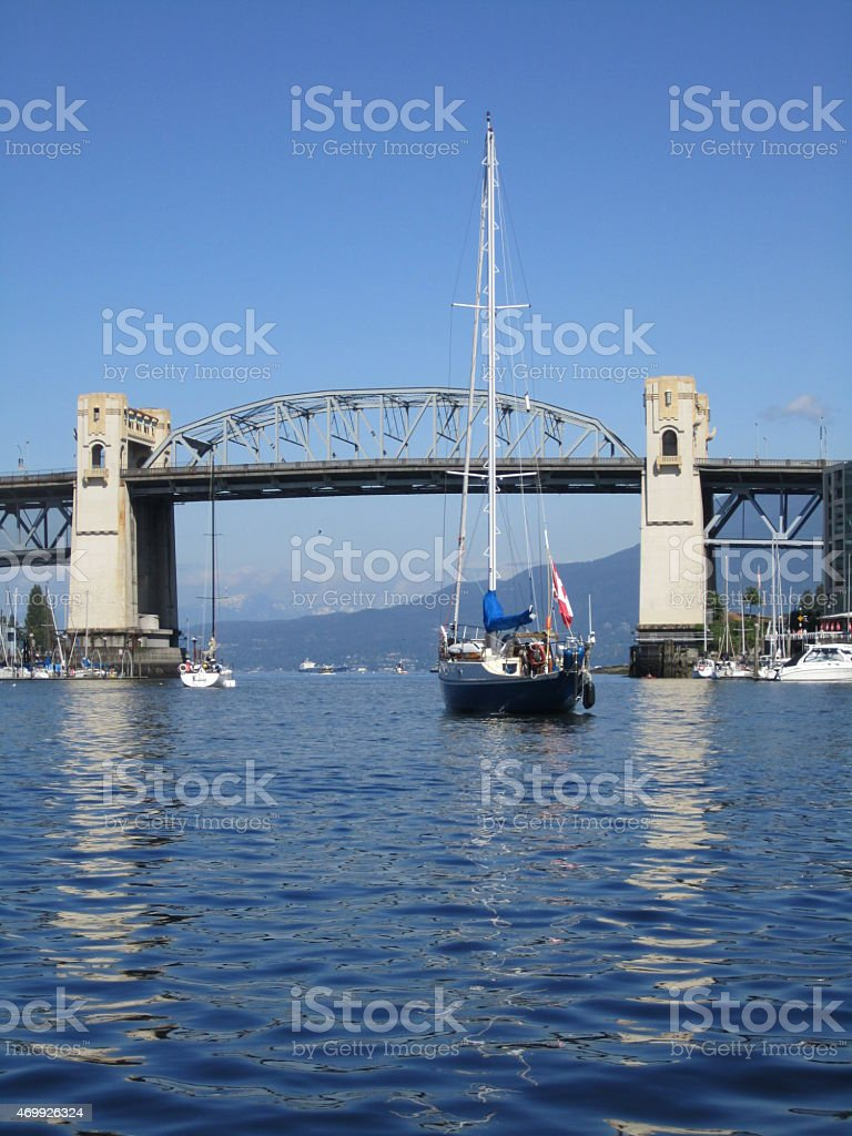 Sail boat heading toward Burrard Street Bridge Vancouver stock photo