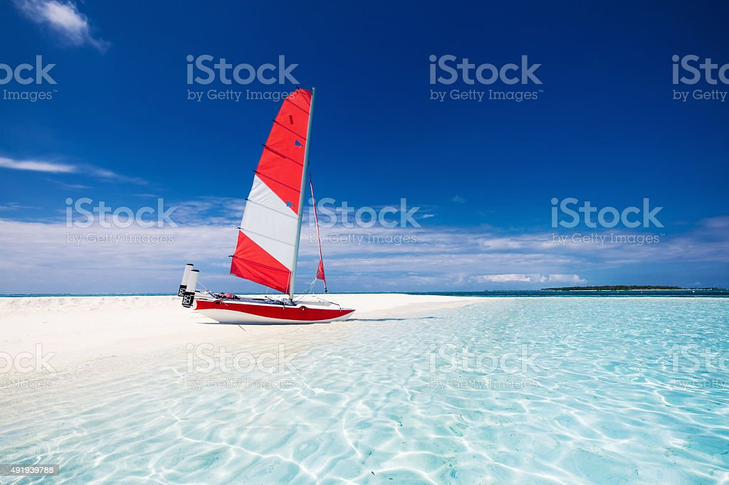 Sail boat with red sail on a tropical beach stock photo