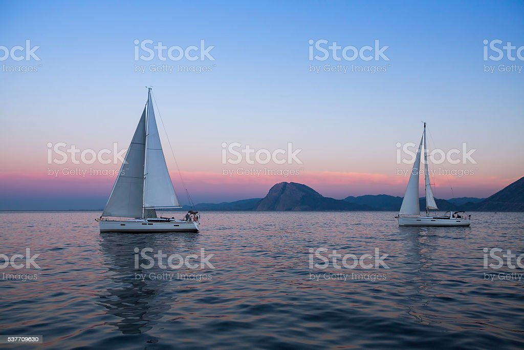 Sail boats near the rocky shores after amazing sunset. stock photo