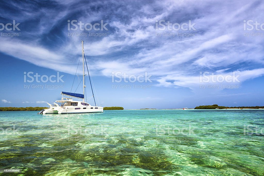 Sailboat anchored at a tropical turquoise island stock photo