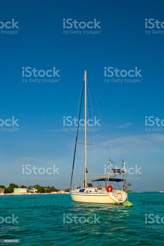 Sailboat anchored on a tropical island royalty-free stock photo