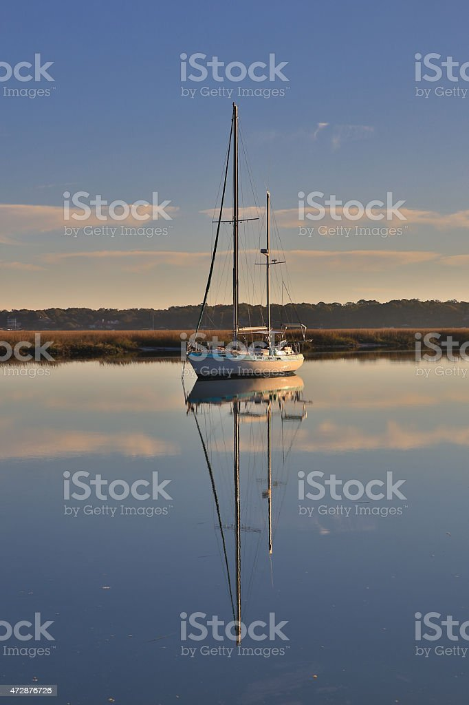Sailboat and its reflection on the water stock photo