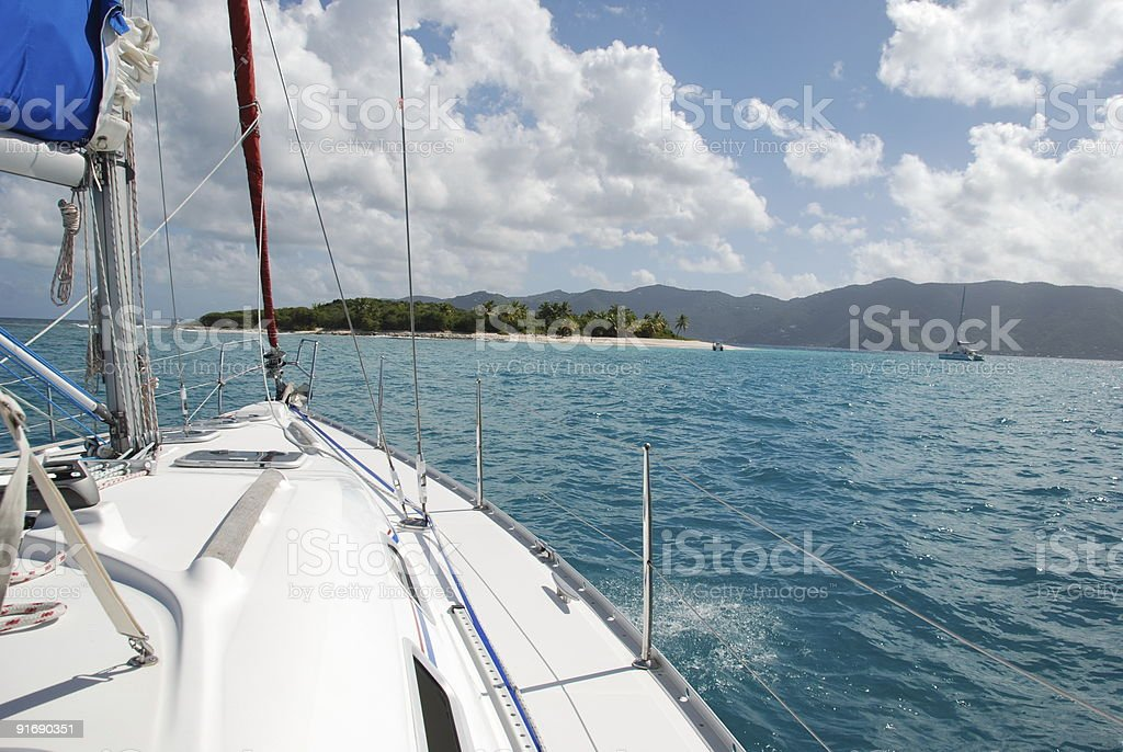 Sailboat approaching deserted cay royalty-free stock photo