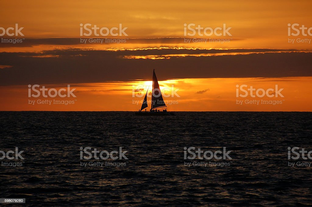 Sailboat at Sunset in Cabo San Lucas stock photo
