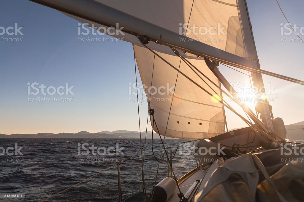 Sailboat at sunset ocean stock photo