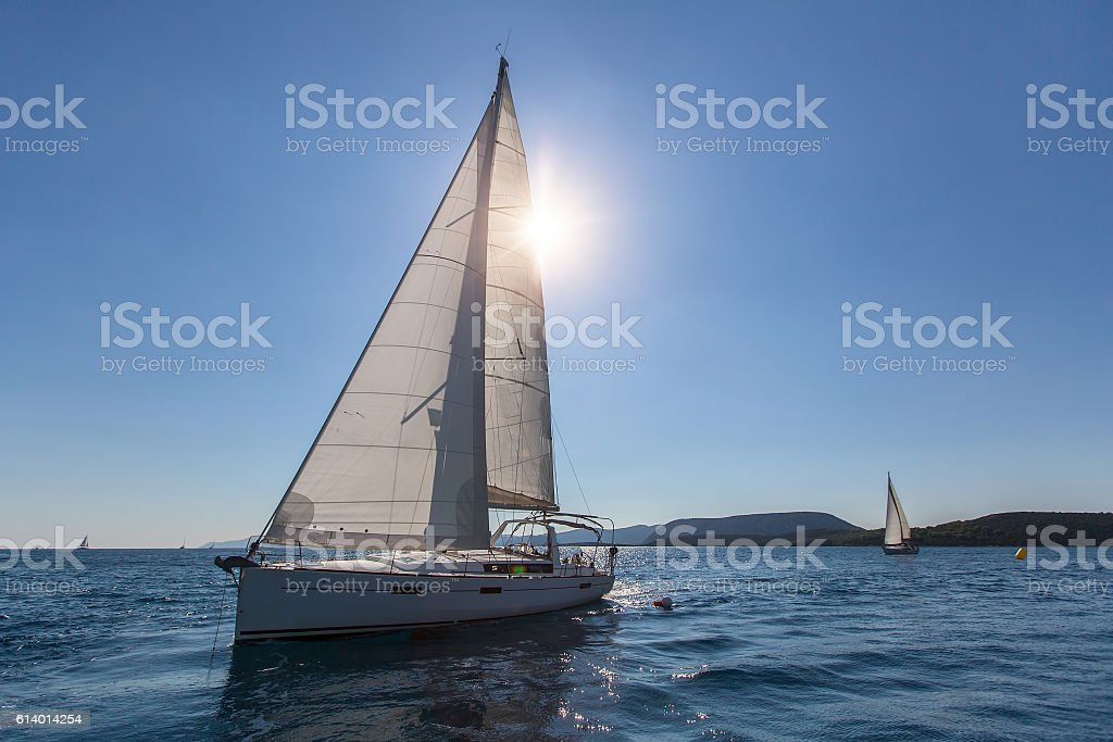 Sailboat at the finish regatta race in the backlight. stock photo