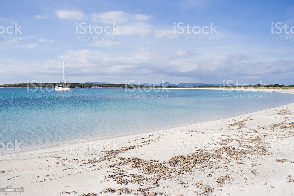 Sailboat by the unspoild beach. royalty-free stock photo