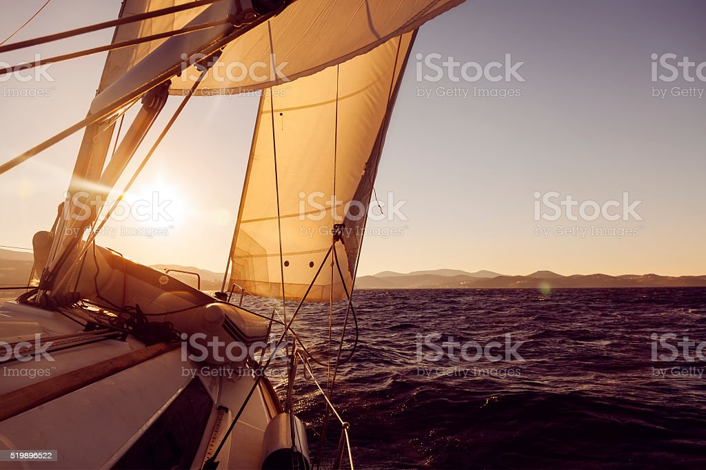 Sailboat crop during the regatta at sunset ocean stock photo