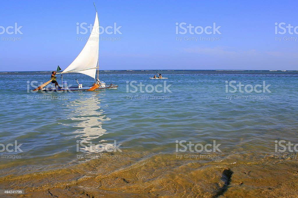 Sailboat crossing water in Northeastern Brazil paradise beach stock photo