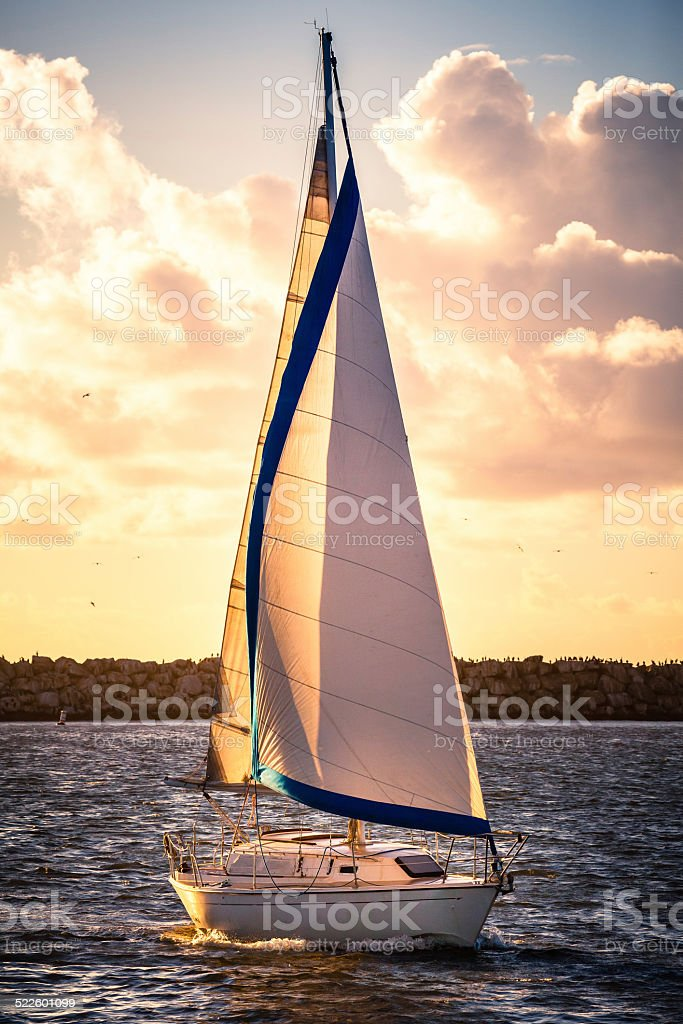 Sailboat Entering The Marina As The Sun Is Setting royalty-free stock photo