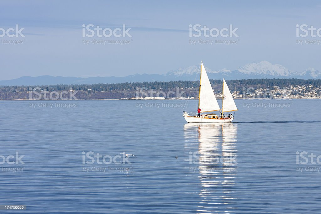 Sailboat ghosts along on glassy water stock photo