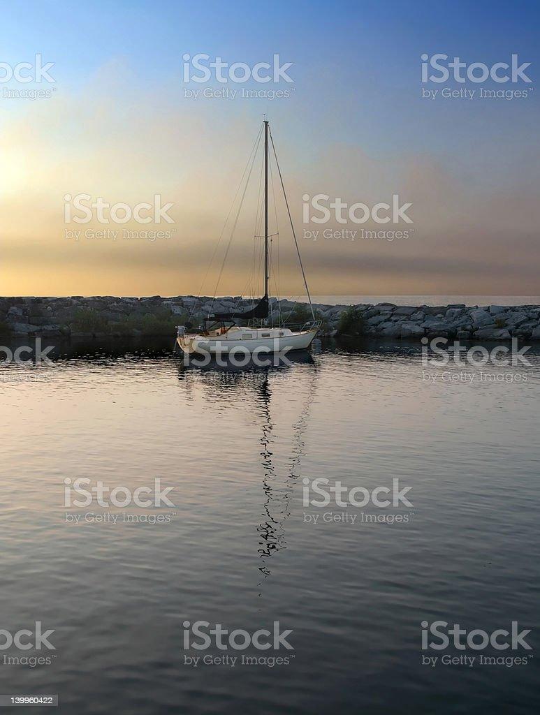 Sailboat in harbor at sundown stock photo