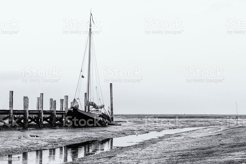 Sailboat in port during low tide stock photo