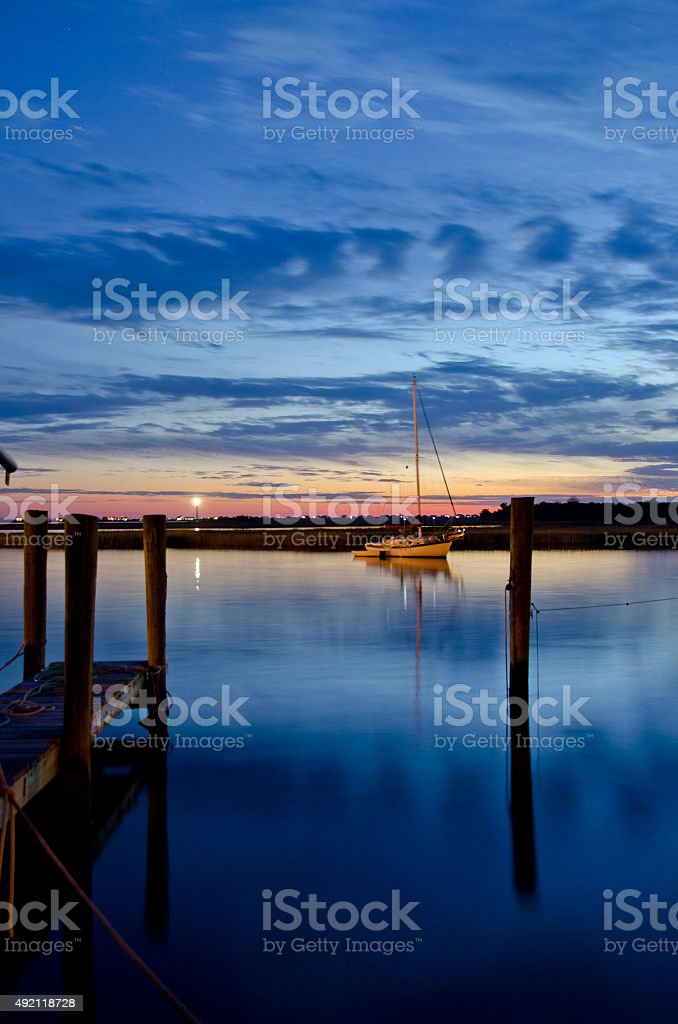 Sailboat in Shimmering Water at Dusk stock photo