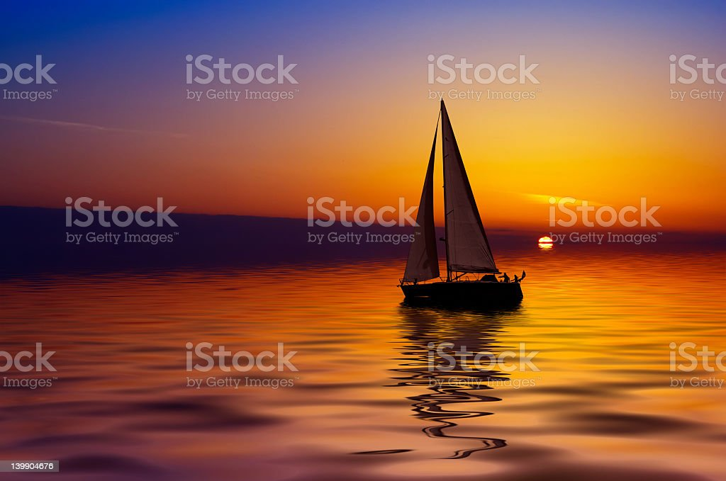 Sailboat on calm water during colorful sunset stock photo