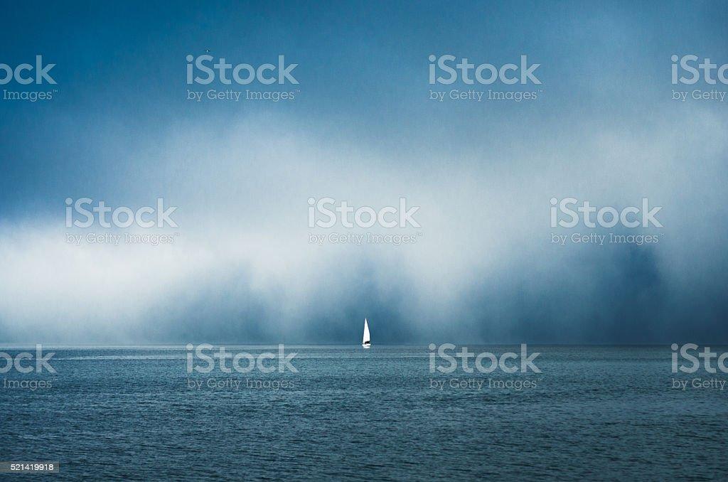 Sailboat on the horizon under mist stock photo