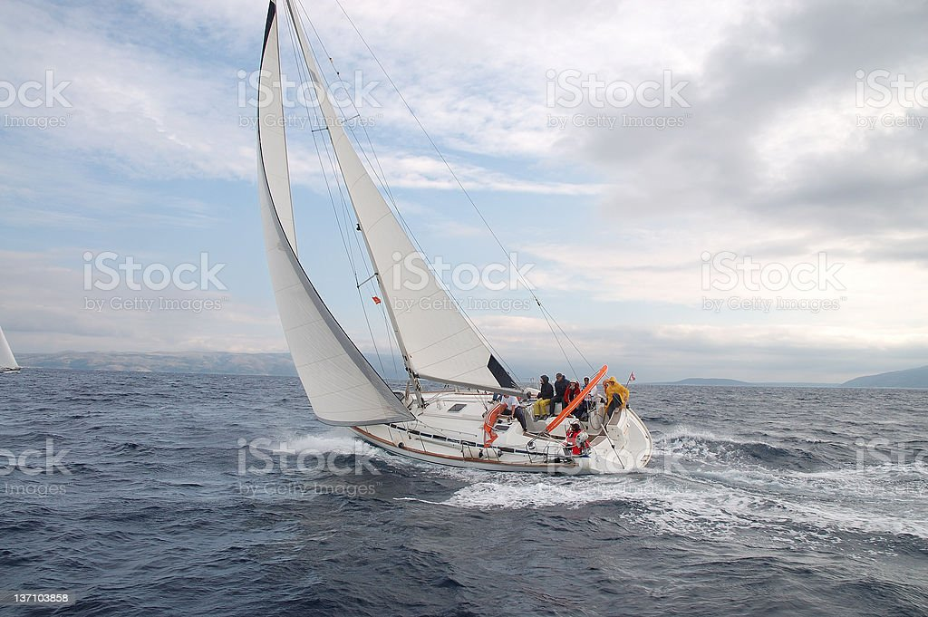 A sailboat on the water cutting through the water royalty-free stock photo