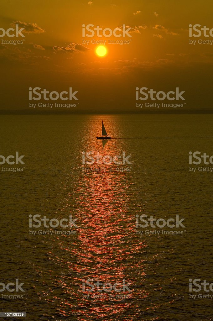 Sailboat Out to Sea at Sunset stock photo