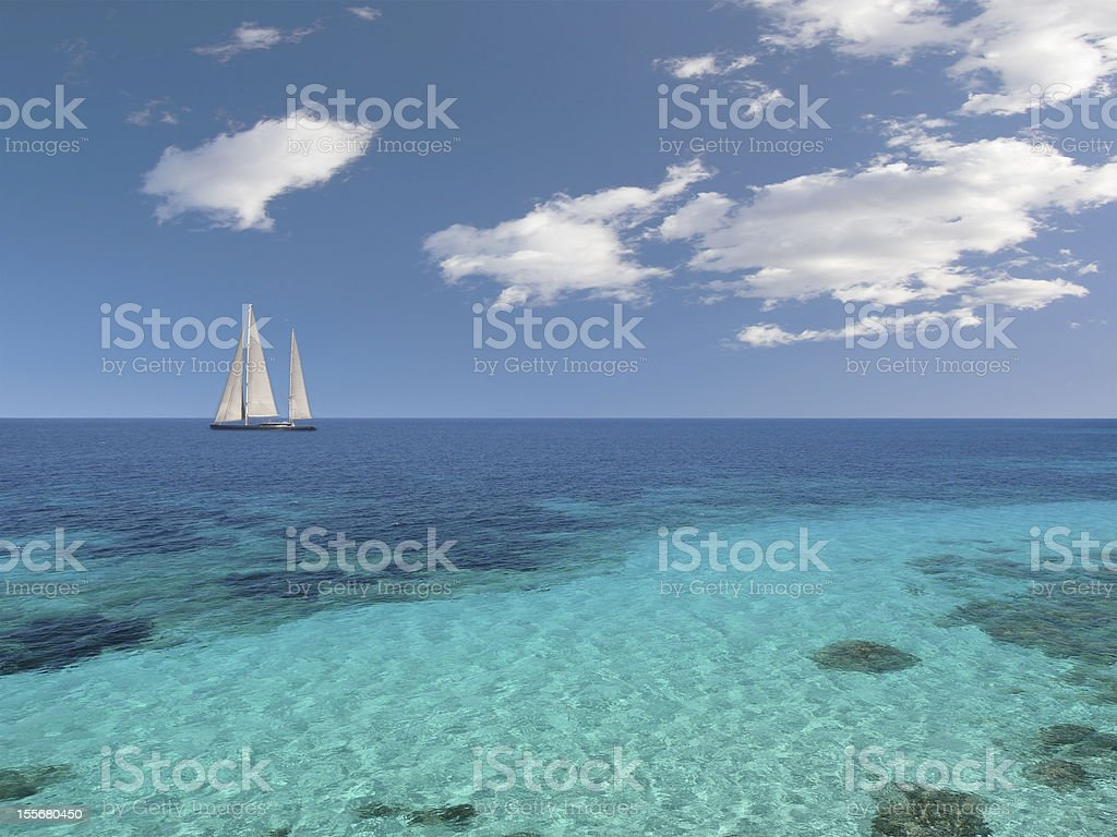 A sailboat out at sea with a beach view stock photo