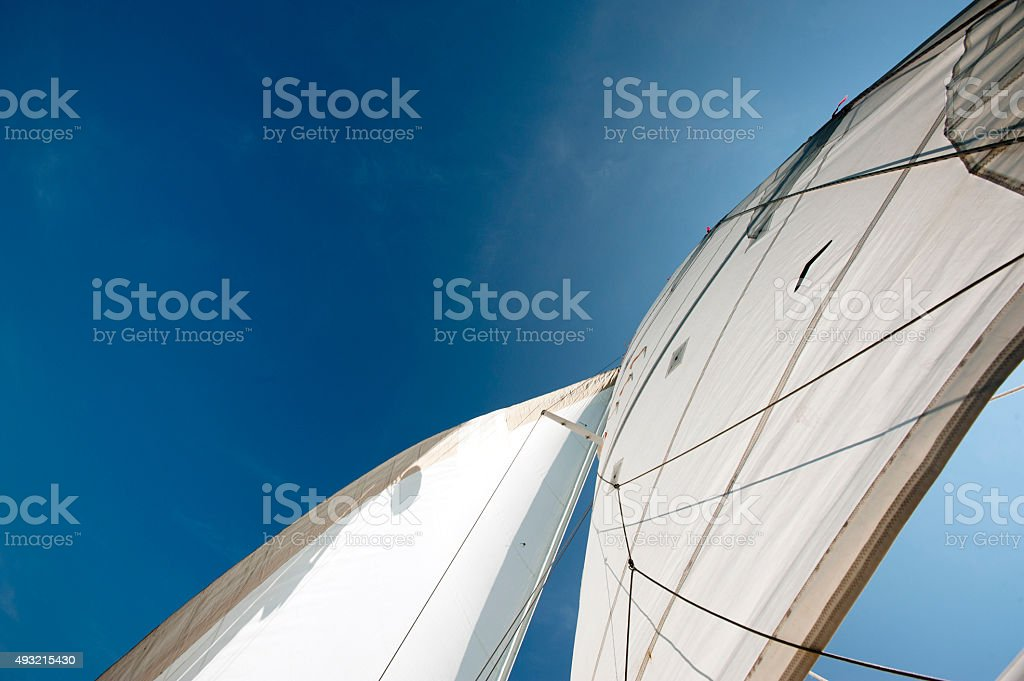 Sailboat sails in the wind and sun stock photo