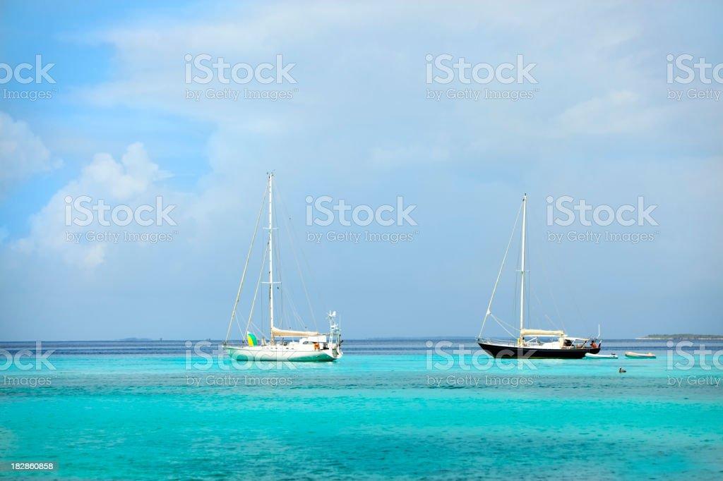 Sailboats anchored on a tropical island royalty-free stock photo