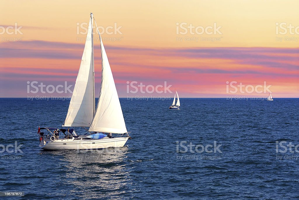 Sailboats at sunset stock photo