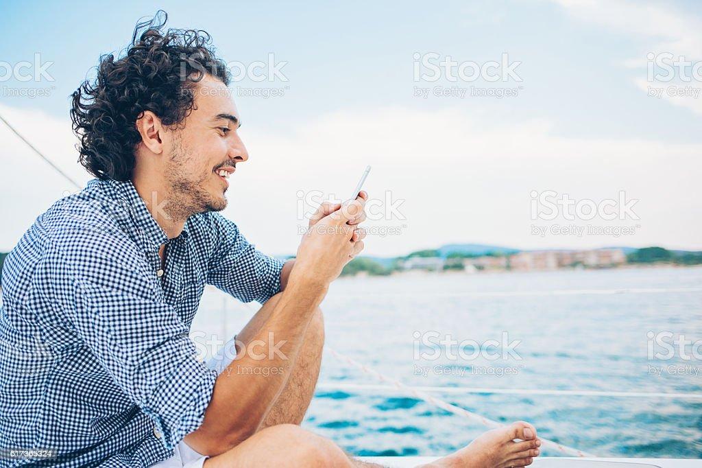 Sailing and texting stock photo