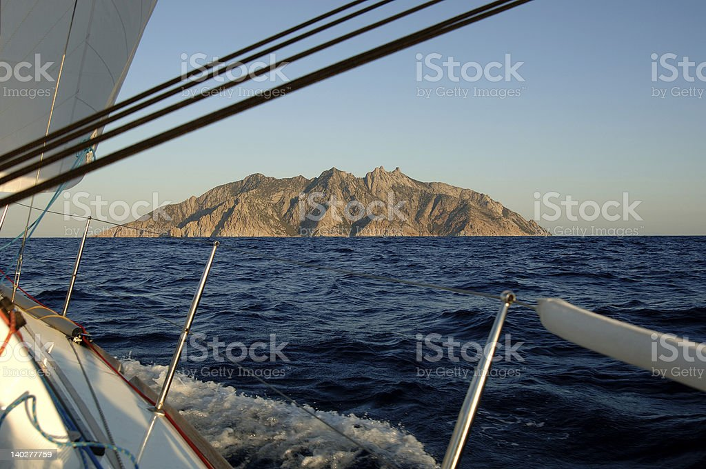Sailing around Montecristo Island at dawn royalty-free stock photo