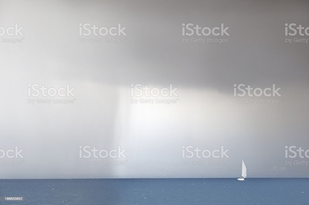 Sailing away from storm stock photo