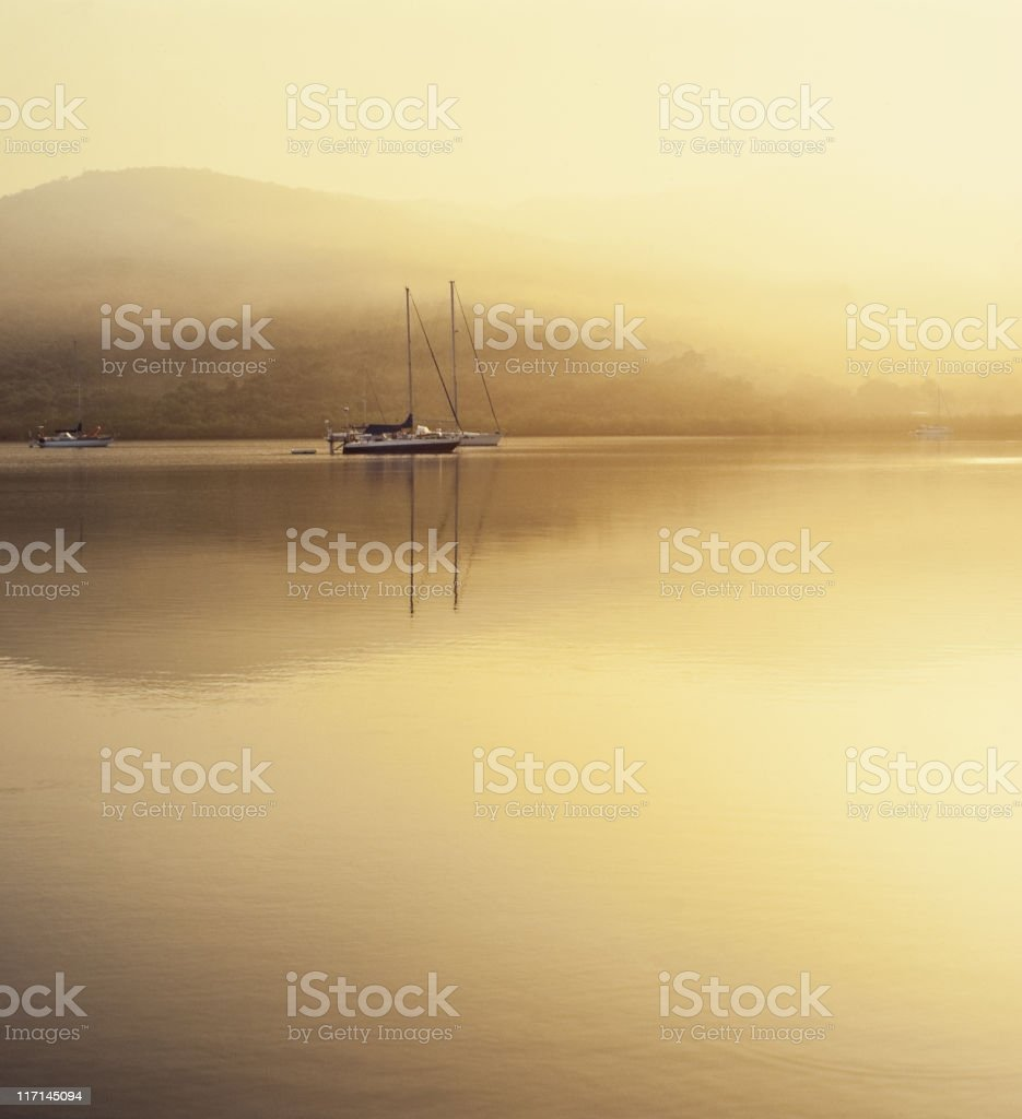 Sailing boat anchored in tropical caribbean bay with fog. royalty-free stock photo